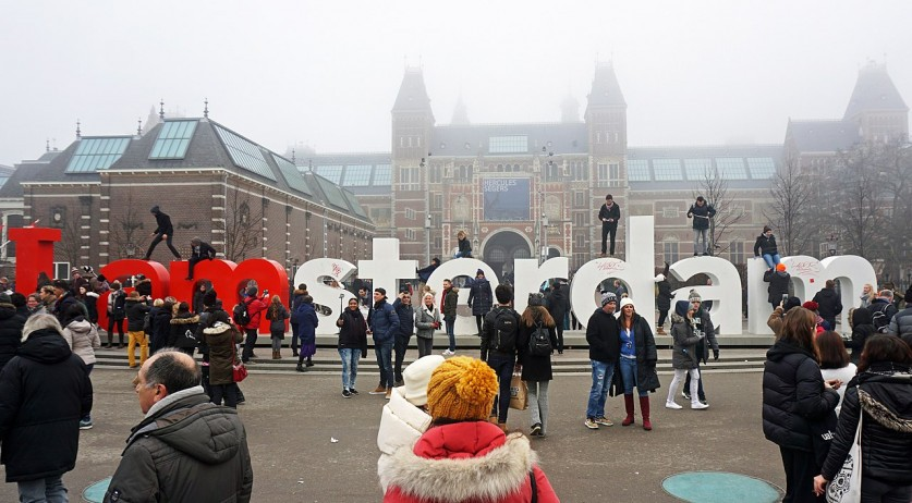 Tourists at the I Amsterdam sign behind the Rijksmuseum
