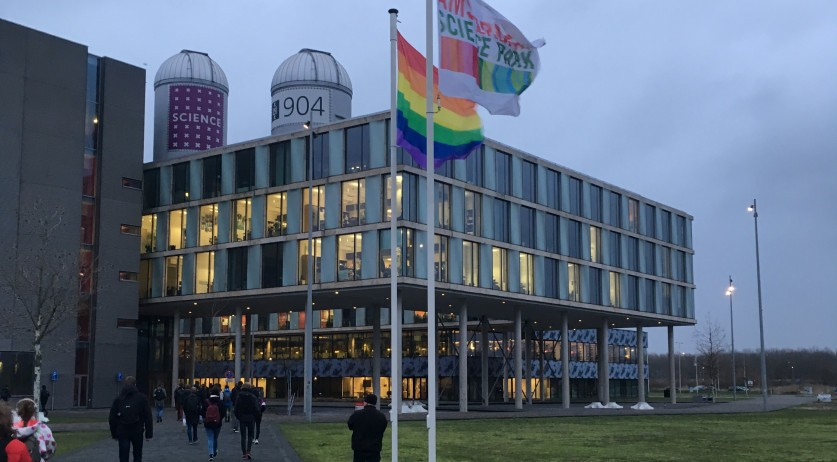 Students walk past a rainbow flag flying above the University of Amsterdam's Science Park campus, 8 Jan 2019