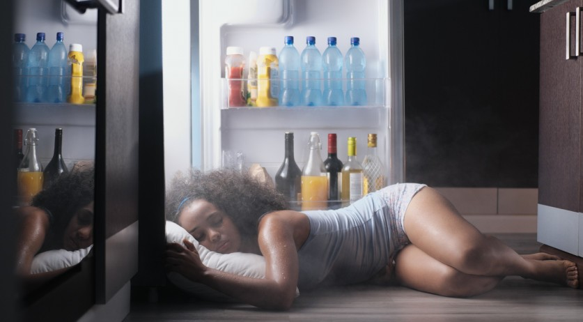 Woman sleeping in front of an open fridge on a hot night
