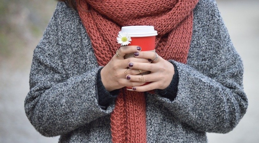 A woman bundled up with a warm drink