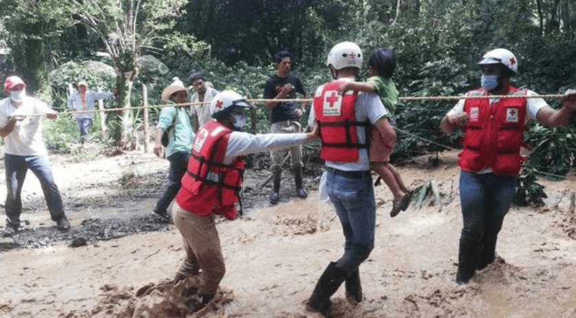 Red Cross rescue workers helping a child after hurricane Eta in Central America