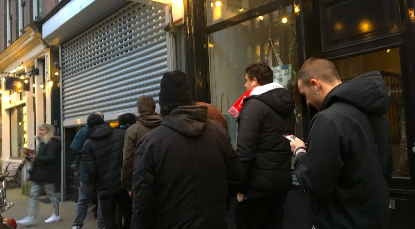 People standing in line outside a coffeeshop set to close for coronavirus regulations