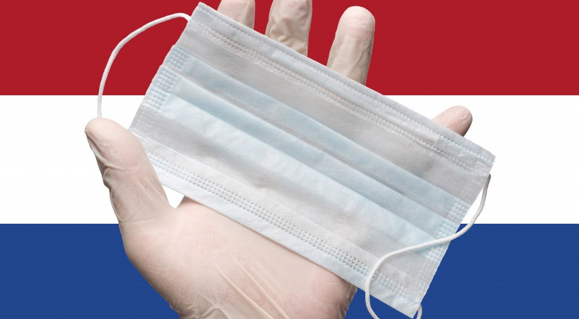Doctor's hand holding a surgical mask in front of the Dutch flag