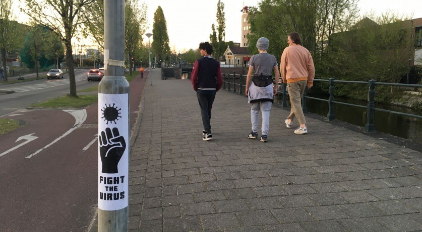 Covid-19: Three young men walk past a 'Fight the Virus' sign on Panamalaan in Amsterdam, 22 April 2020