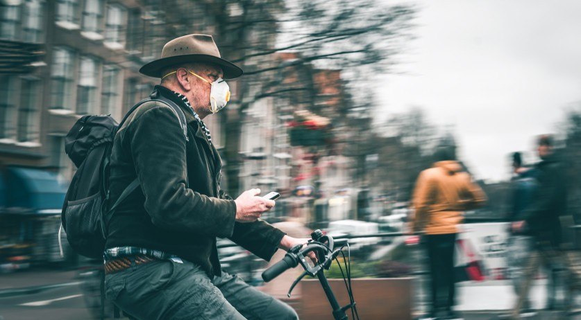 A man cycling through Amsterdam wearing a respirator-style medical mask