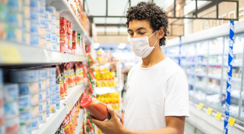 Young man wearing a face mask in a grocery store