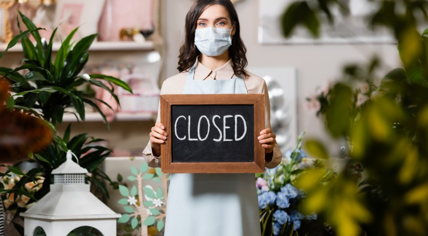 Florit with mask holidng closed sign