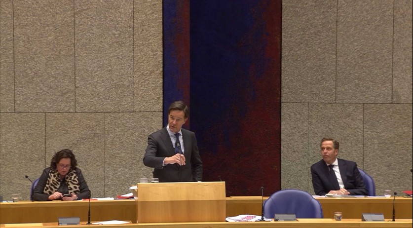Prime Minister Mark Rutte, with Health Ministers Tamara van Ark and Hugo de Jonge behind him, during a parliamentary debate on the Covid-19 vaccination policy, 5 January 2021