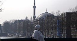 A woman with her head covered stands on an Amsterdam bridge with a mosque in the background