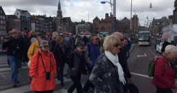 Three groups of tourists on walking tours try to cross the Damrak in Amsterdam Centrum, 13 Apr 2017