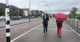 Tourists walk through light morning rain on their way to Amsterdam Centraal, 6 Jun 2017