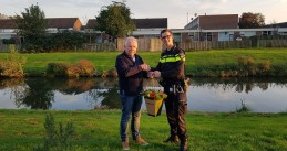 Cees van Loon gets flowers from the Den Bosch police after he saved a toddler from drowning, 19 Oct 2017