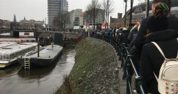 Tourists line up for canal boat tours in Amsterdam
