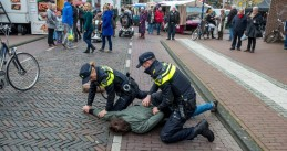Dutch police officers arrest a suspect