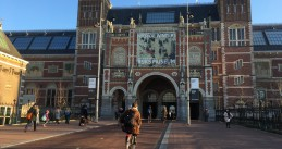 Bundled up bikers entering the Rijksmuseum tunnel under their billboard celebrating the winter season, Amsterdam 7 February 2018