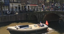 A boat cruising down Oudezijds Voorburgwal in Amsterdam Centrum, 8 May 2018