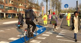 A scooter rider and several bicyclists approach a snorfiets checkpoint in Amsterdam Centrum, 8 April 2019