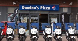 Delivery scooters in front of a Domino's Pizza in The Hague