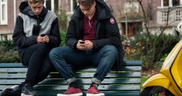 Teenagers using their smartphones on a bench in Amsterdam