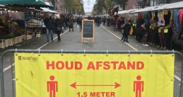 A sign in front of the busy Dappermarkt in Amsterdam Oost reminding people to keep a safe distance from each other. 11 November 2020