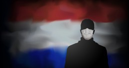 A person in a medical mask in front of the Dutch flag