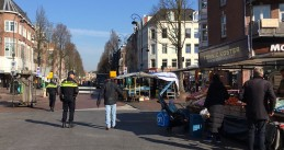 Covid-19: Police patrol the Dappermarkt in Amsterdam to make sure shoppers keep 1.5 meters apart, 26 March 2020