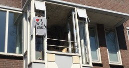 "A shirt hanging in an Amsterdam Oost window stating ""I'm staying here!"""