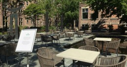 Cafe de Tropen in Amsterdam expanding its terrace into the courtyard of the Tropenmuseum in preparation for terraces reopening on 1 June 2020. Sign asks visitors to not move the tables which were organized with social distancing in mind. 29 May 2020