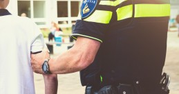 A Dutch police officer arresting a boy